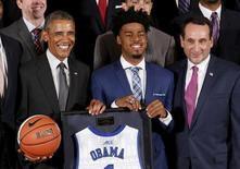 U.S. President Barack Obama holds a basketball and a jersey presented to him by Duke player Quinn Cook (C) and head coach Mike Krzyzewski (R) during an event honoring the 2015 NCAA Champion Duke Blue Devils men's basketball team at the White House in Washington September 8, 2015.    REUTERS/Kevin Lamarque