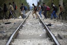 Пакистанские мигранты переходят железнодорожные пути близ греческой деревни Идомени. 9 сентября 2015 года. Евросоюз обеспечит более надежную защиту для беженцев, но в то же время будет укреплять границы и чаще депортировать нелегальных мигрантов, заявил в среду президент Еврокомиссии Жан-Клод Юнкер. REUTERS/Yannis Behrakis