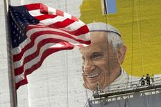 The U.S. flag flies as painters work on a mural of Pope Francis on the side of a building in midtown Manhattan in New York August 28, 2015. REUTERS/Brendan McDermid