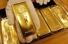 Работник Tanaka Kikinzoku Jewelry K.K. показывает слиток золота в хранилище компании в Токио. 29 января 2008 года. Цены на золото снижаются под давлением сильного доллара, оставаясь в узком диапазоне накануне решения ФРС о процентных ставках. REUTERS/Issei Kato