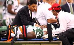Sep 13, 2015; East Rutherford, NJ, USA; New York Jets linebacker Lorenzo Mauldin (55) is carted off the field on a stretcher with team doctors during the second half against the Cleveland Browns at MetLife Stadium. Mandatory Credit: Danny Wild-USA TODAY Sports