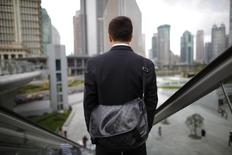 A business man rides an escalator in the financial district of Pudong in Shanghai September 21, 2011. REUTERS/Aly Song