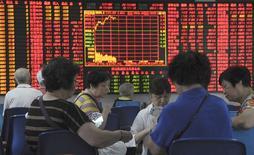 Инвесторы в брокерской конторе в Шанхае. 9 сентября 2015 года. Азиатские фондовые рынки выросли в среду при сниженных объемах торгов накануне решения ФРС о процентных ставках. REUTERS/China Daily