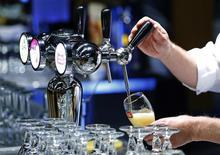 Официант наливает пиво перед встречей акционеров Anheuser-Busch InBev в Брюсселе. 30 апреля 2014 года. Крупнейшая в мире пивоваренная компания Anheuser-Busch InBev проинформировала своего конкурента SABMiller о намерении сделать ему предложение о покупке. REUTERS/Yves Herman