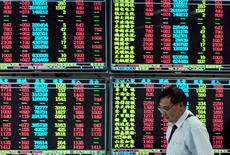 Un inversor camina junto a un tablero electrónico que muestra la información de las acciones, en una correduría en Jiujiang, China, 16 de septiembre de 2015. Las acciones chinas registraron el miércoles sus mayores ganancias en tres semanas, ayudadas por un salto en las últimas operaciones, un fenómeno que muchos operadores creen que es una señal de intervención del Gobierno para impulsar los precios antes de la campana de cierre. REUTERS/China Daily