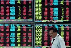 Un inversor camina junto a un tablero electrónico que muestra la información de las acciones, en una correduría en Jiujiang, China, 16 de septiembre de 2015. Las acciones chinas pusieron fin a una semana volátil con una leve alza el viernes, después de que la Reserva Federal de Estados Unidos se abstuvo de elevar las tasas de interés, citando las preocupaciones sobre la debilidad de la economía mundial. REUTERS/China Daily