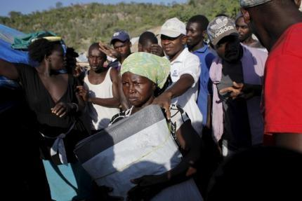 A woman carries tarpaulins to be distributed to fellow residents at a refugee camp for Haitians returning from the Dominican Republic on the outskirts of Anse-a-Pitres, Haiti, September 6, 2015. REUTERS/Andres Martinez Casares