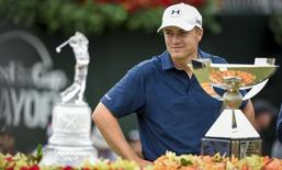 Sep 27, 2015; Atlanta, GA, USA; Jordan Spieth stands with his trophies after winning the final round of the Tour Championship by Coca-Cola at East Lake Golf Club. Mandatory Credit: John David Mercer-USA TODAY Sports