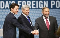 Liberal leader Justin Trudeau, Conservative leader and Prime Minister Stephen Harper and New Democratic Party (NDP) leader Thomas Mulcair (L-R) join hands before the Munk leaders' debate on Canada's foreign policy in Toronto, Canada September 28, 2015.  REUTERS/Mark Blinch