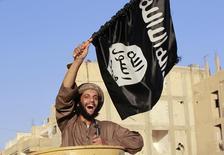 """Боец """"Исламского государства"""" на параде в сирийской провинции Ракка 30 июня 2014 года. США объявили о введении санкций против более чем 30 лидеров """"Исламского государства"""", людей, связанных с финансированием исламистов, оказывающих им поддержку, а также связанных с экстремистами групп в попытке ограничить доступ ИГИЛ к международной финансовой системе. REUTERS/Stringer"""