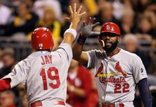 Sep 30, 2015; Pittsburgh, PA, USA; St. Louis Cardinals right fielder Jason Heyward (22) greets center fielder Jon Jay (19) as Jay scores a run against the Pittsburgh Pirates during the seventh inning at PNC Park.  Charles LeClaire-USA TODAY Sports