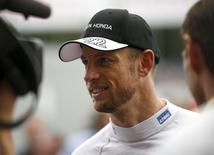 McLaren Formula One driver Jenson Button (C) of Britain speaks to media at paddock area after  the qualifying session of the Japanese F1 Grand Prix at the Suzuka Circuit in Suzuka, Japan, September 26, 2015.  REUTERS/Toru Hanai