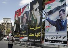 """Предвыборные плакаты Башара Асада в Дамаске. 2 июня 2014 года. Сотни иранских военных прибыли в Сирию 10 дней назад с оружием, чтобы принять участие в наземных операциях на подконтрольных повстанцам территориях на севере страны; ливанская """"Хезболла"""" также готовится присоединиться к операции, сообщили Рейтер ливанские источники в четверг. REUTERS/Khaled al-Hariri"""