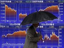 Un hombre que sostiene un paraguas camina delante de un tablero electrónico que muestra el índice Nikkei, afuera de una correduría en Tokio, 8 de septiembre de   2015. El índice Nikkei de la bolsa de Tokio cerró estable el viernes en un débil volumen de negocios, luego de que los inversores se mostraron reacios a tomar posiciones grandes antes de unos datos clave de empleo en Estados Unidos que serán reportados más tarde en el día. REUTERS/Issei Kato