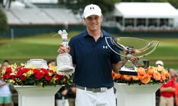 Sep 27, 2015; Atlanta, GA, USA; Jordan Spieth with the tournament trophy and FedEx Cup trophy after winning the final round of the Tour Championship by Coca-Cola at East Lake Golf Club. Jason Getz-USA TODAY Sports
