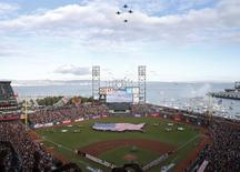 Military F/A-18 Hornet jets fly over a large U.S. flag unfurled on the field during festivities ahead of Game 1 of the MLB World Series baseball championship between the San Francisco Giants and the Detroit Tigers in San Francisco, October 24, 2012.   REUTERS/Stephen Lam