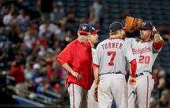 Washington Nationals manager Matt Williams (9), left stands on the mound with Washington Nationals second baseman Trea Turner (7) and Washington Nationals shortstop Ian Desmond (20) during a pitching change in the eighth inning of their game against the Atlanta Braves at Turner Field. The Braves won 2-1. Mandatory Credit: Jason Getz-USA TODAY Sports