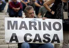 Homem segura cartaz pedindo que Marino, prefeito de Roma, vá para casa.  8/10/2015.  REUTERS/Max Rossi