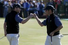 International team members Louis Oosthuizen (L) and Branden Grace of South Africa celebrate their point against U.S. team members Jordan Spieth and Dustin Johnson on the 14th hole during the four ball matches of the 2015 Presidents Cup golf tournament at the Jack Nicklaus Golf Club in Incheon, South Korea, October 9, 2015.   REUTERS/Toru Hanai
