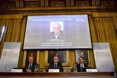 """Una proyección con el rostro del economista Angus Deaton, mientras el secretario permanente de la Real Academia Sueca de Ciencias, Goran K. Hansson (C), y Jakob Svensson, miembro de la academia, ofrecen una conferencia de prensa en Estocolmo, el 12 de octubre de 2015. El economista británico-estadounidense Angus Deaton ganó el premio Nobel de Economía de 2015 por """"su análisis del consumo, la pobreza y el bienestar"""", anunció el lunes la Real Academia Sueca de Ciencias. REUTERS/Maja Suslin/TT News Agency"""