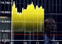 Un peatón se refleja en un tablero electrónico que muestra el índice Nikkei de Japón, afuera de una correduría en Tokio, 27 de agosto de 2015. Las bolsas de Asia se tambaleaban el miércoles, extendiendo las pérdidas después de que la inflación al consumidor en China se enfrió más que lo previsto en septiembre, avivando la inquietud sobre las presiones deflacionarias en la segunda mayor economía del mundo. REUTERS/Yuya Shino