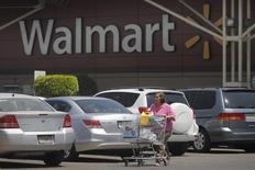 Женщина с тележкой у магазина Wal-Mart в Мехико. 24 апреля 2012 года. Wal-Mart Stores Inc предупредила в среду, что более высокие зарплаты, а также затраты на интернет-торговлю и низкие цены могут сократить прибыль на акцию в следующем году до 12 процентов, что привело к самому стремительному за 25 лет обвалу бумаг компании. REUTERS/Edgard Garrido