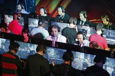 Люди играют в видеоигры на выставке Electronic Entertainment Expo в Лос-Анджелесе 11 июня 2014 года. USM Holdings Алишера Усманова и его партнеры инвестируют в развитие крупнейшего российского сообщества в сфере киберспорта - группы компаний Virtus.pro, объем инвестиций может превысить $100 миллионов, говорится в совместном сообщении компаний. REUTERS/Jonathan Alcorn