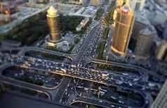 Vehículos pasan por el Puente Guomao durante la hora punta en Pekín, 3 de septiembre de 2014. El crecimiento económico de China se ralentizaría a un 6,5 por ciento en el 2016 a partir de un 6,8 por ciento previsto en el 2015, aún si el banco central relaja adicionalmente la política monetaria, mostró un sondeo de Reuters. REUTERS/Jason Lee
