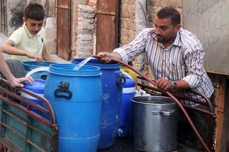 Residents fill containers with water in a rebel-controlled area of Aleppo, Syria July 24, 2015. REUTERS/Abdalrhman Ismail/Files