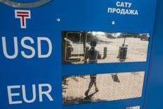 A woman walking on a street is reflected on a switched off electronic board showing the Kazakhstan tenge's exchange rate against the U.S. dollar and euro in Almaty, Kazakhstan, August 20, 2015. REUTERS/Pavel Mikheyev