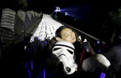 """A fan holding a Stormtrooper helmet from """"Star Wars"""" poses for a photo, in front of five hundred replicas of the Stormtrooper characters at the Juyongguan section of the Great Wall of China during a promotional event for """"Star Wars: The Force Awakens"""" film, on the outskirts of Beijing, China, October 20, 2015. REUTERS/Jason Lee"""