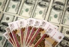 """Рублевые и долларовые банкноты. Сараево, 9 марта 2015 года. Рубль вырос в четверг на фоне позитивной динамики нефти и благодаря продажам экспортной валютной выручки к оставшимся октябрьским налогам, отметившись на сессионных пиках 69,60 за евро и 62,36 за доллар после """"голубиных"""" комментариев главы ЕЦБ Марио Драги. REUTERS/Dado Ruvic"""