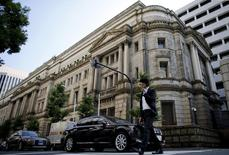 A man walks past the Bank of Japan (BOJ) building in Tokyo, June 24, 2015. The government's backsliding on promises to rein in spending puts the Bank of Japan in a bind, limiting its scope to expand its massive monetary stimulus when the economy needs it, or ultimately to wind it back without causing chaos in the bond markets. Picture taken June 24, 2015.      To match story JAPAN-ECONOMY/BOJ       REUTERS/Toru Hanai - RTR4YZ0O