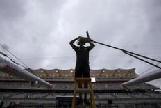 Rain clouds approach as a Red Bull Formula One pit crew member installs a camera ahead of the first practice session of the U.S. F1 Grand Prix at the Circuit of The Americas in Austin, Texas October 23, 2015.   REUTERS/Adrees Latif