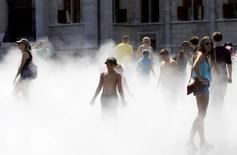 Tourists cool off in water vapor in front of the Hungarian Parliament during a hot summer day in Budapest, Hungary, July 22, 2015. REUTERS/Bernadett Szabo
