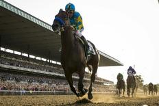 Jockey Victor Espinoza, aboard American Pharoah, rides after winning the 147th running of the Belmont Stakes as well as the Triple Crown, in Elmont, New York June 6, 2015. REUTERS/Lucas Jackson