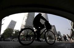 Велосипедист проезжает под мостом в Пекине. 19 октября 2015 года. Китайская экономика может побить прогнозы Международного валютного фонда и вырасти почти на 7 процентов, хотя среднесрочный прогноз менее точен, сказал высокопоставленный представитель МВФ. REUTERS/Jason Lee