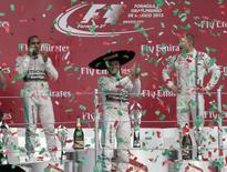 Mercedes Formula One driver Nico Rosberg (C) of Germany celebrates between his teammate Lewis Hamilton (L) of Britain and Williams Formula One driver Valtteri Bottas of Finland after winning the Mexican F1 Grand Prix at Autodromo Hermanos Rodriguez in Mexico City, November 1, 2015. REUTERS/Henry Romero