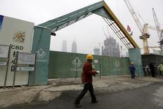 Un trabajado camina delante de la entrada de una construcción de un edificio, en Pekín, China, 26 de octubre de 2015. El crecimiento económico anual de China no será inferior a un 6,5 por ciento en los próximos cinco años a fin de alcanzar la meta de duplicar el Producto Interno Bruto (PIB) del 2010 y el ingreso per cápita para el 2020, dijo el martes el presidente Xi Jinping según citas difundidas por la agencia estatal de noticias Xinhua. REUTERS/Jason Lee