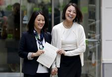 Hiroko Masuhara (L) and her partner Koyuki Higashi hold their partnership certificate as they walk out from the Shibuya ward office after the ward office issued the nation's first same sex partnership certificates in Tokyo, Japan, November 5, 2015. REUTERS/Yuya Shino