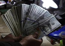 Работник обменного пункта держит долларовые купюры. Манила, 15 января 2014 года. Курс доллара к корзине шести основных валют близок к трехмесячному максимуму накануне выхода отчета о занятости в США, который повлияет на решение ФРС о повышении процентных ставок. REUTERS/Romeo Ranoco