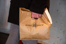 A customer holds a bag full of food inside of a Shake Shack store in New York January 30, 2015. Shares of hamburger chain Shake Shack Inc soared as much as 150 percent in their first day of trading on Friday, valuing the company that grew out of a hotdog cart in New York's Madison Square Park at nearly $2 billion. REUTERS/Lucas Jackson (UNITED STATES - Tags: BUSINESS FOOD) - RTR4NNPQ