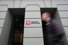 Мужчина проходит мимо здания Московской биржи 7 ноября 2014 года. Снижение российских фондовых индексов немного усилилось к середине дня в отсутствие поддерживающих внешних и внутренних факторов. REUTERS/Maxim Shemetov