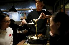 An employee rolls up a pork rib with cheeses as patrons look on, at a restaurant in Seoul, South Korea, October 30, 2015. REUTERS/Kim Hong-Ji