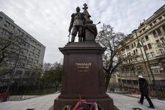 A woman walks past a statue of Czar Nicholas II of Russia, outside the Serbian presidency building in Belgrade, November 27, 2014. REUTERS/Marko Djurica