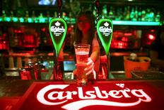 A bartender serves a glass of Carlsberg beer at a bar in Kuala Lumpur, Malaysia in this July 4, 2012 file photo. REUTERS/David Loh/Files
