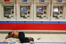 Un vagabundo durmiendo frente a unos cajeros automáticos en la avenida Paulista en Sao Paulo, jun 8, 2014. Un mundo que nuevamente se sintió demasiado cómodo con altos niveles de deuda y pocos incumplimientos de pago podría llevarse sorpresas desagradables el próximo año, y no solo en Estados Unidos.  REUTERS/Damir Sagolj