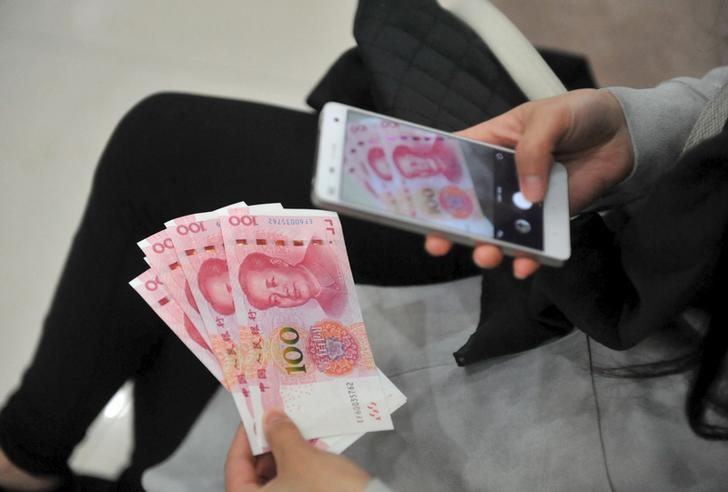 A woman takes pictures of new 100 yuan banknotes she withdrew from a bank in Hangzhou, Zhejiang province, China, November 12, 2015. REUTERS/Stringer