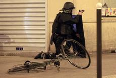 Policial vasculhando veículo suspeito próximo ao restaurante La Carillon, após ataques em Paris.  15/01/2015  REUTERS/Pascal Rossignol