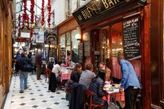 People sit at tables as they have lunch outside bistros in a covered passageway, the Passage des Panoramas, in Paris, France, November 17, 2015.   REUTERS/Charles Platiau